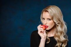 Belle fille blonde dans la robe noire tenant la pomme, regardant l'appareil-photo photo libre de droits