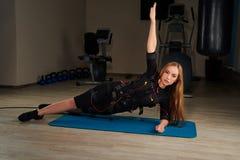Belle fille blonde dans le costume de SME faisant l'exercice latéral de planche sur s Image stock