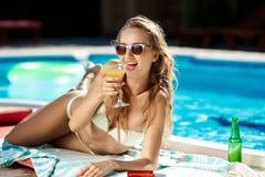 Belle fille blonde dans prendre un bain de soleil de vêtements de bain, se trouvant près de la piscine Images stock