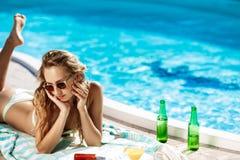 Belle fille blonde dans prendre un bain de soleil de vêtements de bain, se trouvant près de la piscine Photographie stock libre de droits