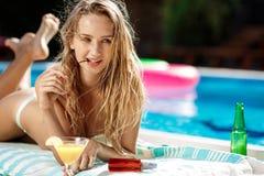 Belle fille blonde dans prendre un bain de soleil de vêtements de bain, se trouvant près de la piscine Photos libres de droits