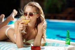 Belle fille blonde dans prendre un bain de soleil de vêtements de bain, se trouvant près de la piscine Photo stock