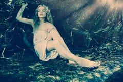Belle fille blonde dans une robe blanche humide en bois sauvage photos libres de droits