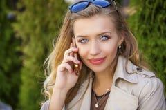 Belle fille blonde heureuse appelant par le téléphone dans une rue d'été Image libre de droits