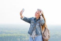 Belle fille blonde heureuse prenant des selfies dehors en parc photos libres de droits