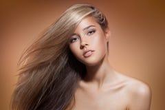 Belle fille blonde Long cheveu sain Fond de Brown Image stock