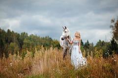 Belle fille blonde mince dans la robe étreignant un cheval gris,  photographie stock libre de droits