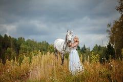 Belle fille blonde mince dans la robe étreignant un cheval gris,  photographie stock