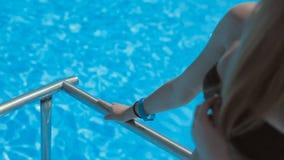 Belle fille blonde mince se tenant près de la piscine banque de vidéos