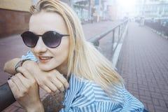 Belle fille blonde posant avec des verres, sur le fond de la ville Jour, extérieur Photo stock
