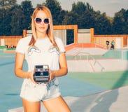 Belle fille blonde posant dans les shorts de denim et le T-shirt blanc avec des lunettes de soleil en parc de patin et prenant de Images stock