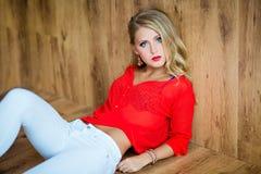 Belle fille blonde sexy dans un chemisier rouge se trouvant sur le plancher photo libre de droits
