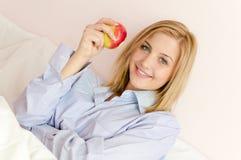 Belle fille blonde sexy de jeune femme tenant l'appareil-photo de sourire de pomme et de regard heureux Photographie stock