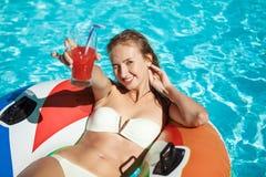 Belle fille blonde souriant, cocktail potable, nageant dans la piscine Images stock