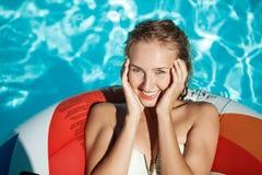Belle fille blonde souriant, se reposant, détente, nageant dans la piscine Image stock