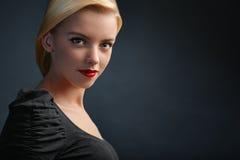 Belle fille blonde sur le fond foncé Image stock