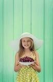 Belle fille blonde sur un fond de mur de turquoise dans le chapeau blanc tenant le plat avec la cerise Images stock