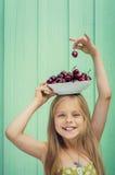Belle fille blonde sur un fond de mur de turquoise tenant le plat avec des cerises sa tête Images stock