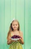 Belle fille blonde sur un fond de mur de turquoise tenant le plat avec la cerise Photo stock
