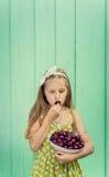Belle fille blonde sur un fond de mur de turquoise tenant le plat avec la cerise Photographie stock libre de droits