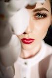 Belle fille blonde tenant des orchidées, lumière du soleil dure, mode photographie stock