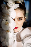 Belle fille blonde tenant des orchidées, lumière du soleil dure, mode image stock