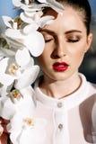 Belle fille blonde tenant des orchidées, lumière du soleil dure, mode images stock