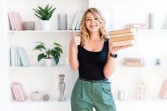 Belle fille blonde tenant une pile de livres et montrant des pouces  Le concept de l'?ducation, cours, examens images stock