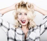 Belle fille blonde utilisant une chemise de plaid montrant la langue et saisie ses mains dans ses cheveux Images stock