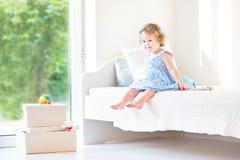 Belle fille bouclée d'enfant en bas âge s'asseyant sur un lit blanc Images libres de droits
