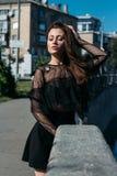 Belle fille, brune, pendant l'été par la rivière dans la ville, dans une robe noire debout seulement par la rivière, le soleil br image stock