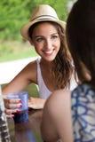 Belle fille buvant dans la barre de piscine avec l'ami Photo libre de droits