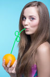Belle fille buvant du jus d'orange par une paille Images stock