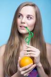 Belle fille buvant du jus d'orange par une paille Photo stock