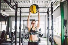 Belle fille caucasienne tenant une boule dans le gymnase Habillé dans le dessus et les shorts image libre de droits