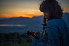 Belle fille causant sur le smartphone au coucher du soleil au-dessus du lac images libres de droits