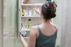 Belle fille choisissant des produits de beauté de l'étagère de salle de bains photo libre de droits