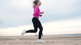 Belle fille courant sur la plage contre la formation de forme physique de côte clips vidéos