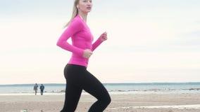 Belle fille courant sur la plage contre la formation de forme physique de côte, femmes européennes dans les écouteurs clips vidéos