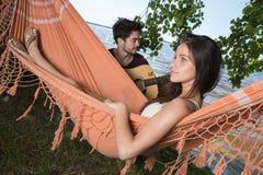 Belle fille détendant dans l'ami de écoute d'hamac jouant la guitare Image stock
