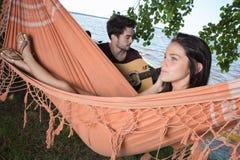 Belle fille détendant dans l'ami de écoute d'hamac jouant la guitare Photographie stock
