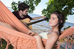 Belle fille détendant dans l'ami de écoute d'hamac jouant la guitare Photo stock