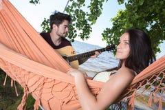 Belle fille détendant dans l'ami de écoute d'hamac jouant la guitare Photos stock