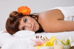 Belle fille détendant sur la table de massage Photographie stock libre de droits