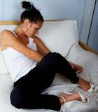 Belle fille détendant sur un sofa blanc Images stock
