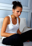 Belle fille détendant sur un sofa blanc Photographie stock