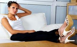 Belle fille détendant sur un sofa blanc Images libres de droits