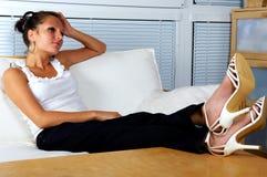 Belle fille détendant sur un sofa blanc Photo stock