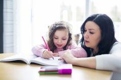 Belle fille d'école faisant des devoirs avec la mère à la maison photo stock