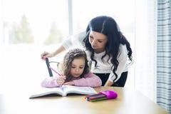 Belle fille d'école faisant des devoirs avec la mère à la maison images stock